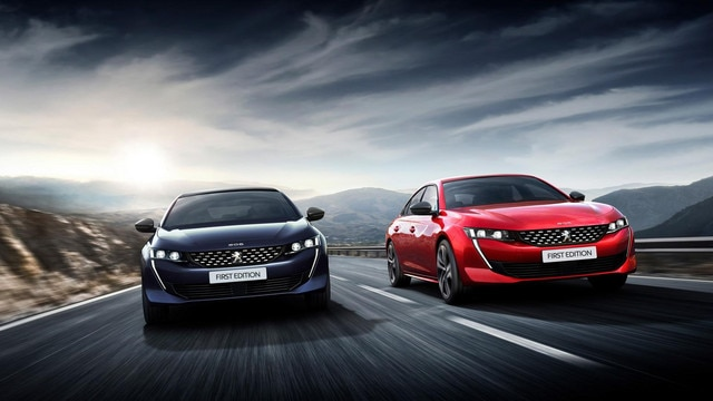 Two Peugeot 508 saloons on road
