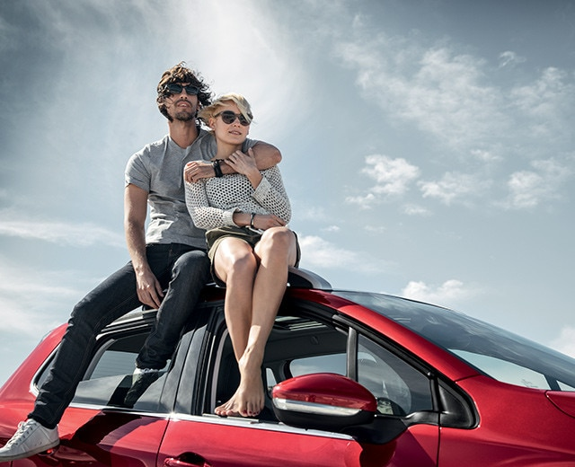 Couple sitting on roof of Peugeot 2008 SUV