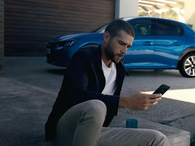 NEW PEUGEOT e-208 - Man with smartphone, MyPeugeot app