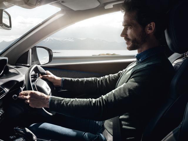 Man driving Peugeot car